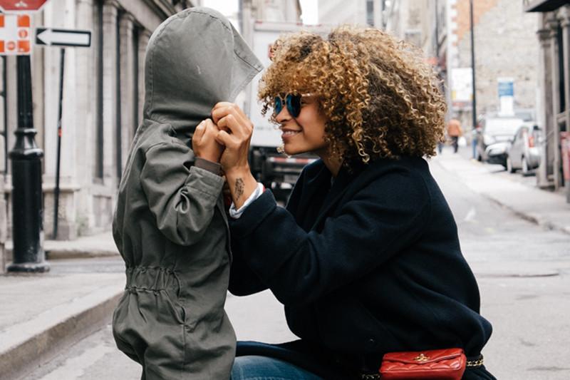 Eine Frau zieht einem Jungen eine Kapuze auf